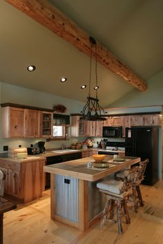 Log cabin kitchen with corrugated metal island.