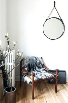 Reading nook with hanging round mirror and faux fur on armchair
