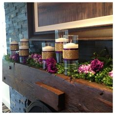 Purple, Lavender and Gold Wedding Inspiration ~  The mantle with a garland of smilax greenery, stock, lisianthus, and cylinders of floating candles. Each cylinder sparkled a bit with a ribbon wrap of purple and gold.  On either side of the fireplace were gold dusted willow trees with hanging crystal strands and purple stock.  From: http://jensblossoms.wordpress.com/2013/06/25/purple-lavender-ivory-gold-real-wedding-gig-harbor-wedding-canterwood-golf-club/