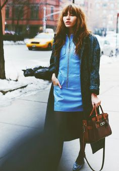 Natalie Suarez wears a blue dress with pocket detailing, a printed coat, tights, and slingback shoes