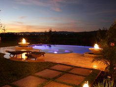 Fire features adorn this infinity pool and add warmth and entertaining value to the outdoor space. The dual fire bowls combine with water to spill over into the pool for a beautiful combination of the elements.