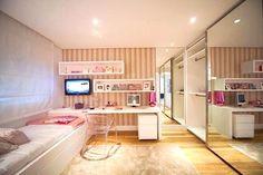 quarto de Quarto de menina com cama encostada na parede + bancada de estudo branca com fundo de papel de parede listrado + cadeira de acrílico transparente + arqmário com portas de correr espelhadas. Lindo, lindo!