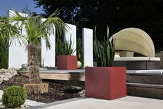 The fibreglass flowerpot CUBO with its matt surface in red decorates a garden area. Fore more red plant pots made of fibreglass see: https://www.planters-online.co.uk/planters-fibreglass-flower-pots/?p=1&o=swag_default_sort&n=48&f=1039.