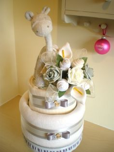 Neutral 2 tier nappy cake with sock bouquet and giraffe topper.