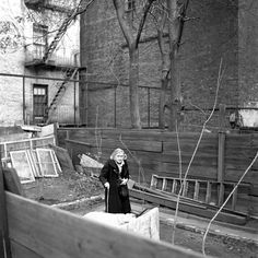 An old woman walking with a cane in a back yard area. 1953, New York, NY