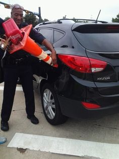 Police Officer Using Orange Traffic Cone To Put Gas In Car.