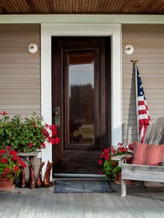 This front porch welcomes guests with a slice of Americana: an Adirondack chair, geraniums, and a flag.