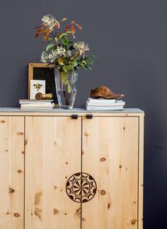 """Die Kommode """"Guarda Val"""" ist aus unbehandeltem Engadiner Arvenholz gefertigt, als Abdeckung dient eine Platte aus Valser Schiefer – Graubündner Möbelbau in seiner schönsten Form. Die Tür schmückt ein traditionelles Sonnenradsymbol. Dass die Kommode dennoch nicht altbacken wirkt, ist ihrer kubischen Form zu verdanken, die ganz ohne verspielte Details auskommt. In verschiedenen Größen erhältlich"""