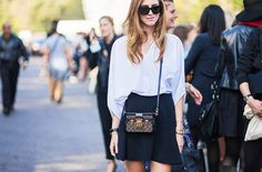 White blouse tucked into a black mini skirt with a cross body bag