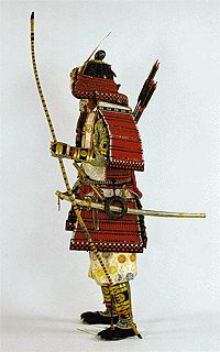 """A """"tsurumaki (=cane ring)"""", a """"shigeto"""" bow, a """"sakatsura"""" arrow case, and """"soya"""" arrows.  The figure in the photograph has a """"gun sen (=military fan)"""" of the Rising-Sun flag in his hand; he wears a """"nae eboshi"""" cap under the helmet and a suit of """"yoroi hitatare"""" under the armor.  """"yoroi hitatare"""" is worn under a """"nae eboshi"""" cap and armor"""