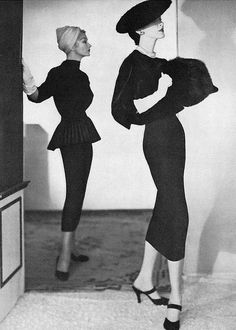 1953 Two forms of slenderness by Traina-Norell, Lisa (l) in black silk crepe tunic sharply pleated, Dovima  in black velveteen blouson top and wool skirt, hats by Emme, photo by Horst, Vogue