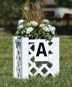 Olympia Lattice Flower Boxes with snap-on letters and flower basket arrangement. Boxes are built with a sturdy plant shelf.