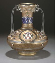 AN ENAMELLED GLASS MAMLUK STYLE VASE FOR THE MIDDLE EASTERN MARKET, PROBABLY FRANCE, 20TH CENTURY  Of flattened globular form with tubular neck and two loop handles, the body painted in enamel colours and gold with a wide band of floral roundels between gold panels with further floral decoration, the neck with a pseudo-Arabic inscription in enamels-14¾in. (37.5cm.) high