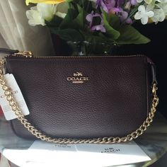 Coach Nolita Pebble leather 19 Large wristet NWT. Coach Nolita pebble leather. Authentic guaranteed. Oxblood color with gold chain. Brand new from pet and smoke free Home. Cheaper at MERC Coach Bags Clutches & Wristlets
