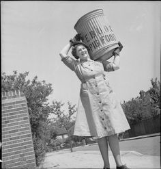 http://ww2today.com/wp-content/uploads/2013/04/pig-food-collection.jpg Pig Food: Women's Voluntary Service Collects Salvaged Kitchen Waste, East Barnet, Hertfordshire, England, 1943. A full-length portrait of Kathleen Kent, carrying a pig bin on her shoulder, on a sunny street during her daily rounds. Kathleen is the head of the pig food collection unit at East Barnet.