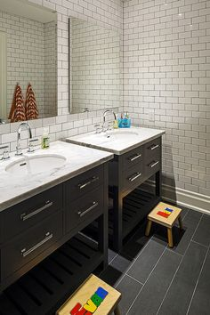 Fun kids' bathroom features side-by-side black washstands with Italian Carrara Marble tops, Restoration Hardware Hutton Single Washstands, framed by ceiling height subway tile backsplash accented with dark grout and paired with frameless beveled mirrors on monogrammed step stools over gray staggered tiled floor.