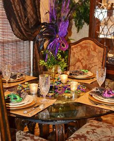 Southern Charm: Mardi Gras Tablescape  napkin rings are inexpensive masks in purple and green. These were a dollar each!!   For the centerpiece,used an old Kirland's tall votive holder. I place a chunk of styrofoam in it and stuck in two small green sparkly picks at the base and fanned them out. I then stuck in a tall Mardi Gras mask that had a stick on it that you hold it with. threw some old beads around the bottom, along with two plastic fleur de lis ornaments and votives.  DONE!