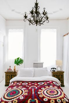 Bright bedroom with bohemian bedding and a chandelier White monochrome with dark chandelier, deep green plant