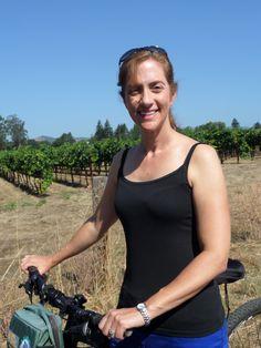 Author Kristen Harnisch biking through the Carneros vineyards in 100-degree heat with Napa Valley Bike Tours! So much fun!