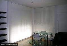 Ventanales de un salón vestidos con un juego de cortina vertical. Dado que estilizan los ambientes, son muy funcionales  y su marcada discreción, las cortinas verticales son cada vez más demandadas para entornos minimalistas y modernos. Aquí, otro ejemplo.
