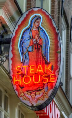 """La Virgen de Guadalupe"" sacred and profane neon sign of a steak house in…"