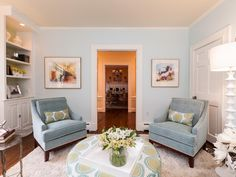 Matching beautifully, this living space is picture perfect. Blue chairs accent the pale blue wall color. The bright white molding and white area rug help the light colors to stand out among a pastel palette.