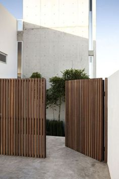 karien anne - outdoors - wooden garden gate leading to a minimal white building