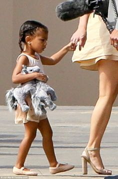 Presents: North, in pink ballet shoes, got a little treat at the track as she was seen carrying two brand new gray plush ponies
