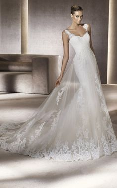 Embroidered sheath gown with a chapel-length train by PRONOVIAS. Available at Elizabeth Johns.
