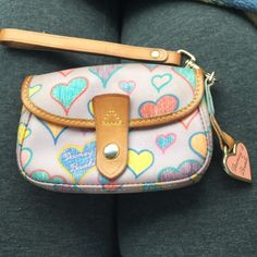 Authentic Dooney&Bourke Heart Vinyl Wristlet Good but used lavender purple with crayon like hearts pattern in multi colors and brown leather trim. Key fob metal attached and canvas white lines interior. Light staining from use but no tears inside or out. Slight pink transfer on back left topside. Prices according to oops. Great Wristlet that holds a lot. Smartphone fits up to size iPhone6. Gold hardware. Dooney & Bourke Bags Clutches & Wristlets