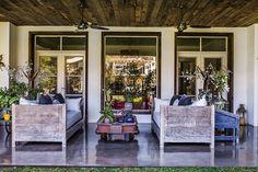 Galería de una casa con camastros de lapacho y almohadones que enmarcan una zorra minera como mesa ratona. Detrás, una carretilla y un mueble azul de taller dan apoyo a macetas y jarrones con plantas (todo de Pablo Ledesma).