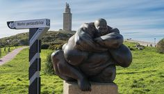 """The giant sculpture of """"Queronte"""" by the artist Ramón Conde, with the Tower of Hercules in the background (the most important symbol of the city of La Coruña - Galicia) is located on a hill near the city in Spain introduces us to Charon. In the Greek mythology, Charon was the mythical boatman who led the souls of the dead by the sacred river Acheron (the river of Hades) and who was paid with an obolium (gold coin) ~.~ Ramones, Hades, Greek Mythology, Hercules, Statues, Garden Sculpture, Spain, Around The Worlds, Tower"""