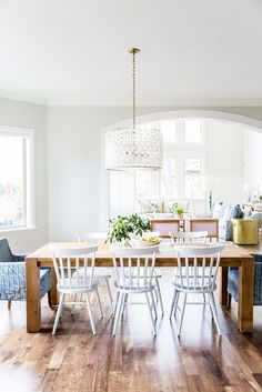Light-filled dining nook with a farm style table, white chairs, and a shell chandelier