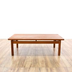 This danish modern coffee table is featured in a solid wood with a vibrant red teak finish. This simple coffee table has straight legs, stretcher sides and curved edges. Sleek table perfect for a small living room! #danishmodern #tables #coffeetable #sandiegovintage #vintagefurniture