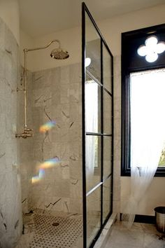 Inspiration from Bathrooms.com: Factory window + marble + rainfall shower head = super stylish. From Porchlight Interiors.  #bathrooms #shower rooms #wet rooms #ensuite #vintage style #industrial style #loft living