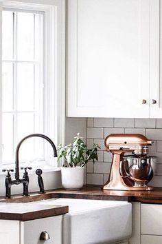 White cabinets, farmhouse sink, bronze faucet, dark butcher block counters. Copper Kitchenaid.