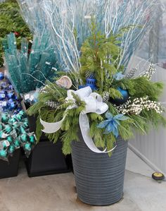 Outdoor evergreen planter with blue and white accents.