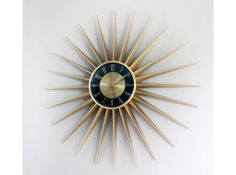 The Sunburst clock has twenty-four gold colored aluminum rays radiating out from a round central core. Matching gold colored minute and hour hands sweep out time over a black and gold dial face with gold numbers.