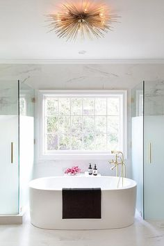 Chic master bathroom boasts oval freestanding tub and a brass vintage tub filler placed under a window illuminated by a brass urchin flush mount flanked by a frosted glass shower to the left and a frosted glass water closet to the right.