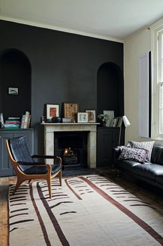 The back parlor is differentiated from the front by charcoal gray walls. The Turkish kilim came from London textile specialists Larusi and the leather sofa is a Robin Day classic from Habitat. Baldwin and Wynn worked with architect James Engel of Spaced Out Architecture Studio on the remodel, which included restoring interior shutters in every room.