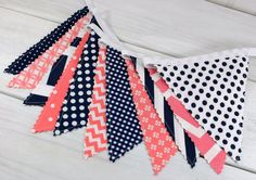 Coral Pink and Navy Blue Chevron, Dots and Stripes make up this adorable Fabric Bunting! ~ The 11 flag Bunting Banner measures 6 feet long ~ The 15 flag Bunting Banner measures 8 feet long ~ The 18 flag Bunting Banner measures 9 feet long ~ The 22 flag Bunting Banner measures 12 feet long Each flag is double sided and measures 6 inches wide and 6 inches tall. The bunting banner has an additional 18 inches of ribbon on each side for tying. ~Would add the perfect finishing touch to your bab...