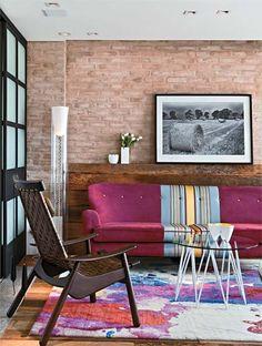Na sala de estar, o piso de madeira avança sobre a parede de tijolos, criando um apoio para a fotografia de Marcio Scavone. Desenhado por Galeazzo, o sofá no estilo dos anos 1950 foi revestido de veludo e ganhou um charmoso detalhe de seda (Donatelli). Poltrona da Dpot, mesa de centro da Conceito Firma Casa, luminária da Kartell e tapete da By Kamy.
