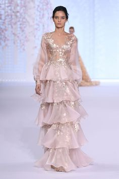 Pale pink silk organza gown with tiered layers and bell sleeves, appliquéd with rose gold taffeta laser cut flowers.