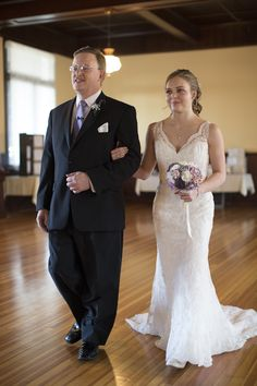 Bride walks down the aisle at an indoor wedding with her father