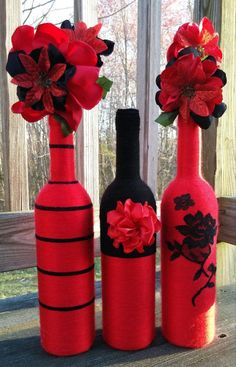 Three wine bottles wrapped in red and black yarn. Accessorized with a red, handmade satin flower...embellished with a black lace floral design. #handmadehomedecor