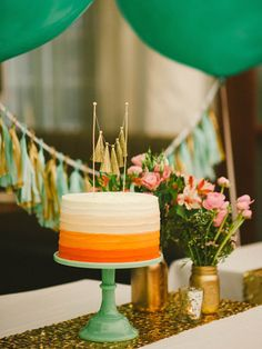An ombre cake—featuring a cute gold tassle cake topper—adds an extra punch of color to the dessert table.