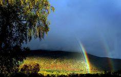 A rainbow and sunshine on a glen south of Kingussie, Scotland