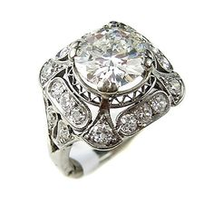 An art deco diamond and platinum ring centering a round transitional-cut diamond weighing 2.00 carats, within a square openwork gallery of transitional-cut diamonds
