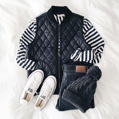 A striped tee under a puffer vest, skinny jeans, sneakers, and a beanie.