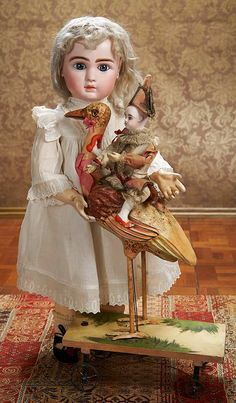 """. Wonderful French Paper-Mache Pull Toy """"Polichinelle Riding a Stork"""" 20"""" (51 cm.) h. 10""""l. Posed upon a wooden platform with four spoked wh..."""